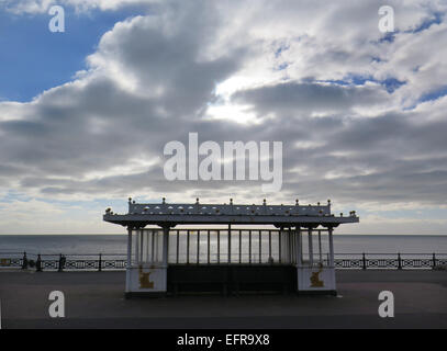 Cumulus clouds gather over a seafront shelter on  Hove Lawns promenade, Brighton and Hove, East Sussex. - Stock Image