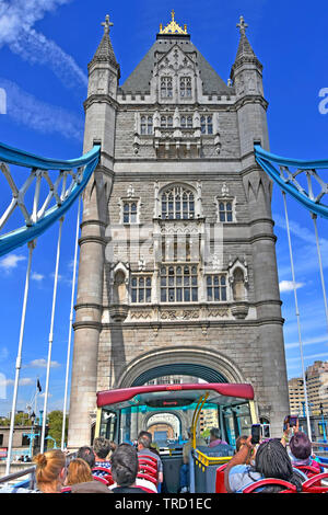 Open top double decker tourist bus back view of passengers on summer sightseeing tour on Tower Bridge taking photos on blue sky day London England UK - Stock Image