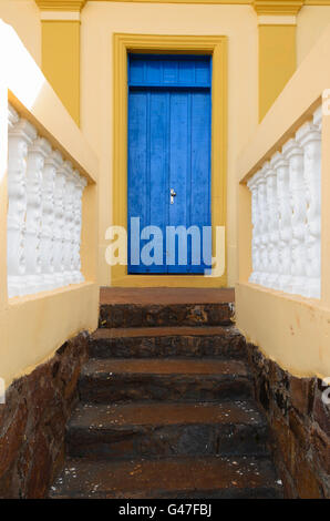 detail of a facade of a house with blue door and staircase made of stone - Stock Image