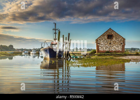 Sunrise and high tide coinicide at Thornham creek. - Stock Image