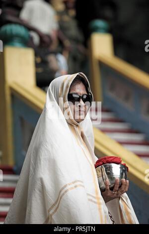 Female kavadi bearer standing on Batu Caves steps during Thaipusam festival in Selangor, Malaysia - Stock Image
