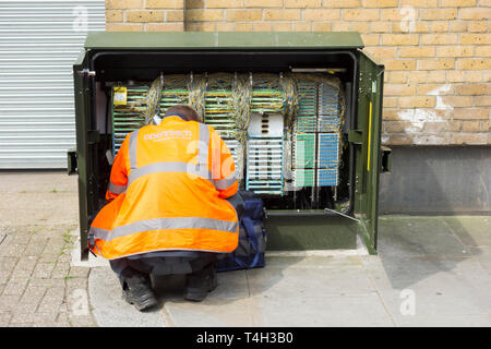 A BT Openreach engineer in front of a telephone cabinet on a street in the UK - Stock Image