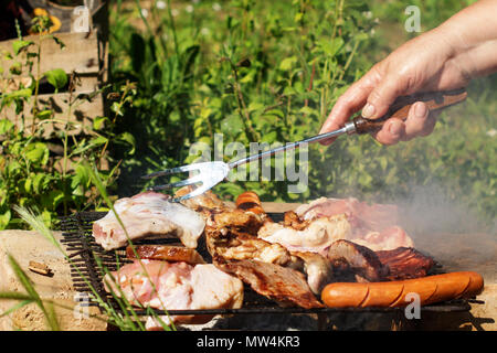 Barbecue. Sausages, chicken thighs, pork steaks and a bacon on a grill grate. An old female hand is using a fork to turn a piece of meat. - Stock Image