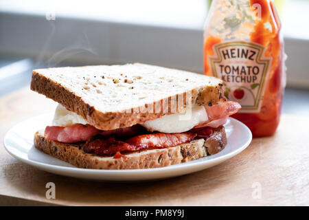 A classic, traditional, delicious, english egg and bacon sandwich made with brown bread - Stock Image