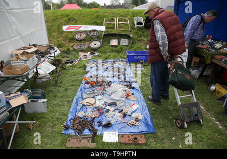 A person looks at parts for sale at the Spring Autojumble at the National Motor Museum in Beaulieu, Hampshire. - Stock Image