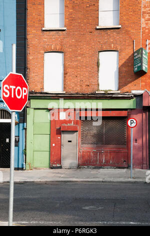 Street view of an empty building/house with windows blocked up and signs of decay yet colourful and interesting in an abstract way, Dublin, Ireland. - Stock Image
