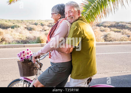 beautiful aged couple of senior in vacation go both on an old bike and enjoy the summer sunlight. tropical place and country side desert in background - Stock Image