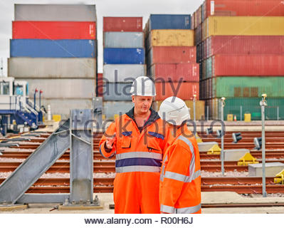 Dock workers talking by railroad tracks - Stock Image