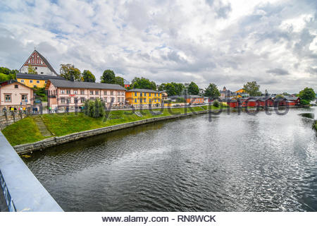 Tourists walk along the Porvoonjoki river adjacent to the medieval village and waterfront homes of Porvoo, Finland in early autumn - Stock Image