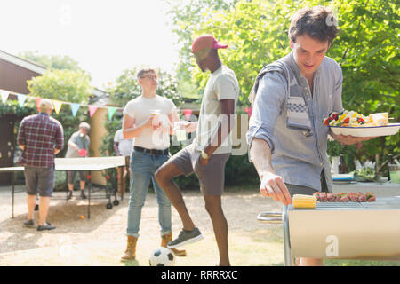Male friends enjoying summer backyard barbecue - Stock Image