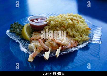 Healthy grilled shrimp on wood skewers with rice pilaf on blue table background is nutrient rich and tasty. - Stock Image