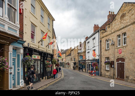 People walking along Market Street Hexham Northumberland with county flags flying - Stock Image