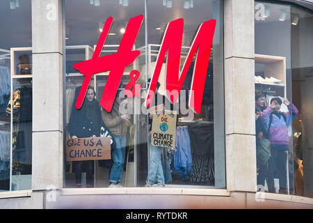 Brighton, UK. 15th Mar, 2019. Protesters get inside a H&M fashion store as thousands of students schoolchildren and parents march through Brighton as they take part in the second Youth Strike 4 Climate protest today as part of a co-ordinated day of global action. Thousands of students and schoolchildren are set to go on strike at 11am today as part of a global youth action protest over climate change Credit: Simon Dack/Alamy Live News - Stock Image