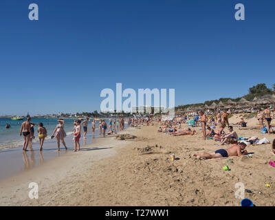 Blue sky, sandy beach, warm Mediterranean sea and a crowd of holiday makers in the sun, a normal day in Ayia Napa Cyprus - Stock Image