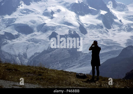 A climber studying a prospective route on a mountain with binoculars, Swiss Alps - Stock Image