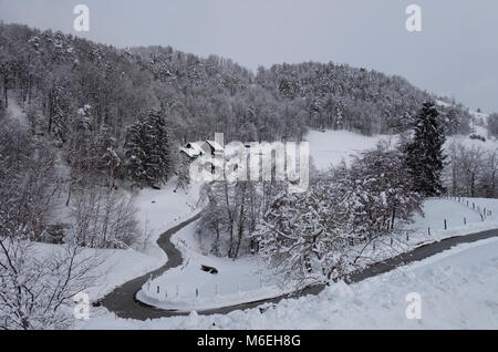 Snow covered landscape with a homesteade in wintertime. Savinjska region ; Stajerska (Steiermark) Slovenia - Stock Image
