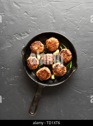 Cooked cutlet in frying pan over black stone background with copy space. Top view, flat lay - Stock Image