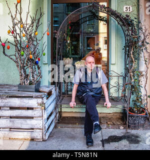 Berlin.Mitte. Senior Elderly man sitting on bench next to Easter egg Tree - Stock Image