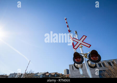 North American level crossing with its typical road sign, saltire shaped, and red and white fences barriers, taken on the port of Montreal railway sys - Stock Image
