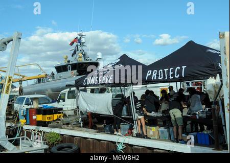 Alongside the moored Sea Shepherd's high speed patrol ship, the 'Ocean Warrior', Sea Shepherd members - Stock Image