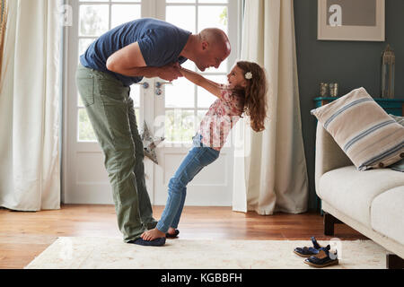 Girl balancing on father's feet at home, side view - Stock Image