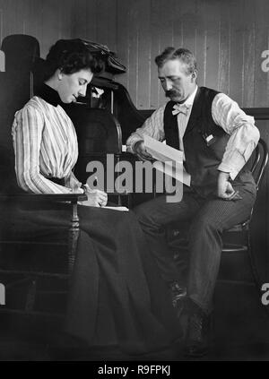 A businessman dictates to his female secretary, ca. 1905. - Stock Image