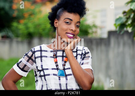 portrait of smiling young woman with hand under chin and looking at camera. - Stock Image