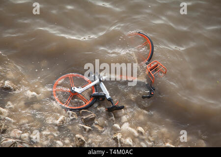 River water laps over a discarded Mobike hire bike thrown into the River Thames by vandals by  Westminster Bridge - Stock Image