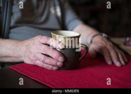 Hands of senior man holding pottery mug - Stock Image