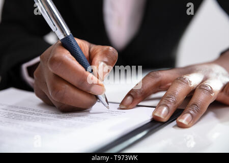 Businesswoman Signing A Contract In The Office - Stock Image