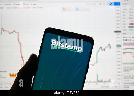 MONTREAL, CANADA - APRIL 26, 2019: Bitstamp cryptocurrency exchange logo and application on Android Samsung Galaxy s9 Plus screen in a hand over a lap - Stock Image