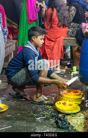 Vertical view of a young boy washing plates in the streets of Kolkata aka Calcutta, India. - Stock Image