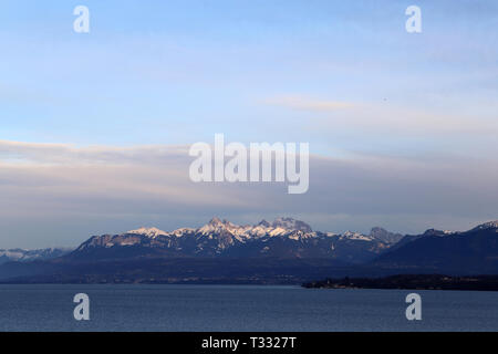 Amazing landscape from Nyon Switzerland representing the time of sunset. You can see the Alps and some clouds above those mountains. - Stock Image