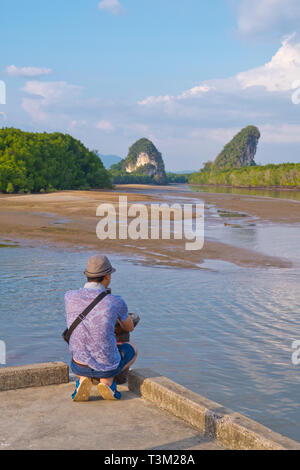 Tourist taking a photo, towards Khao Khanap Nam, State Park viewpoint, Krabi town, Thailand - Stock Image