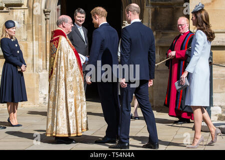 Windsor, UK. 21st April 2019. The Duke of Sussex, followed by the Duke and Duchess of Cambridge, shakes the hand of the Dean of Windsor, the Rt Revd David Conner KCVO, as he arrives to attend the Easter Sunday Mattins service at St George's Chapel in Windsor Castle. Credit: Mark Kerrison/Alamy Live News - Stock Image