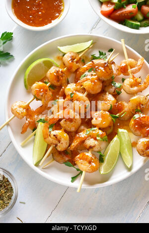 Tasty healthy seafood. Prawns skewers with greens, spices, lime and sauce on white plate over wooden table. Grilled shrimp skewers. - Stock Image