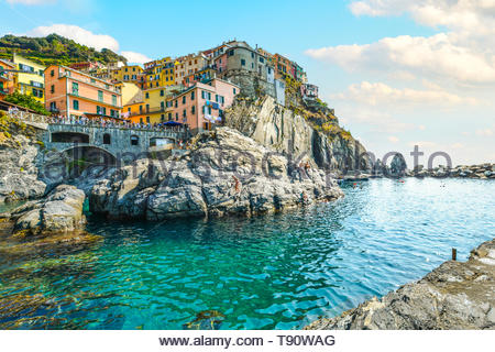 Tourists enjoy the Ligurian sea on a sunny day in early autumn at the resort village or Manarola, Italy, part of the Cinque Terre, an Unesco site - Stock Image