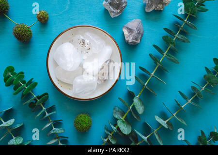 Clear Quartz and Eucalyptus on Turquoise Table - Stock Image