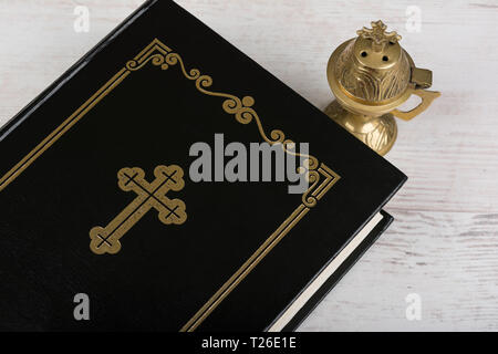 Closeup of Holy Bible and incense burner on white wooden background. Religion concept and faith. - Stock Image