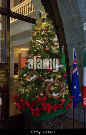Christmas tree outside the Fullerton bay hotel Singapore with flag of Australia nearby - Stock Image