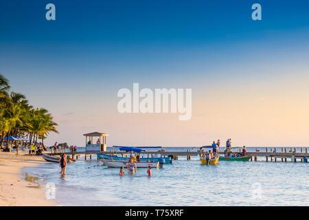 People enjoying a warm evening sunset at West Bay Roatan Honduras - Stock Image