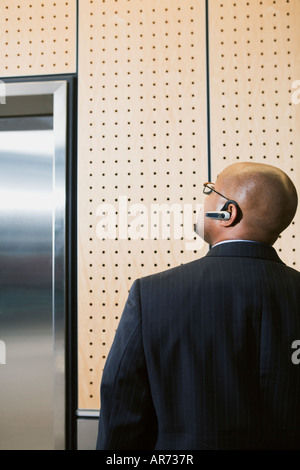 African businessman looking at elevator - Stock Image