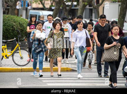 People walking on the streets of Shanghai in China - Stock Image