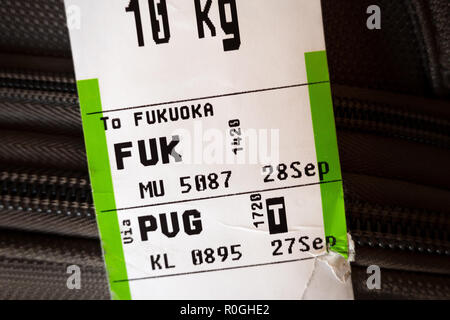 Checked baggage with airline luggage tags showing it's going from Shanghai PVG to Fukuoka FUK airports. - Stock Image