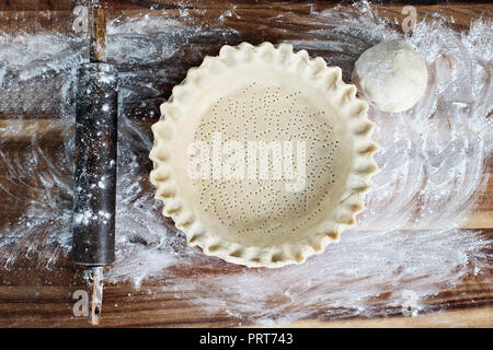 Homemade butter pie crust in pie plate with fluted pinched edge, rolling pin and extra ball of dough over floured rustic wooden background. Crust has  - Stock Image