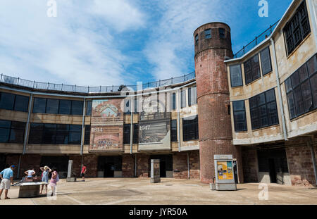 Inner courtyard of Castle Williams, Governors Island, New York City, USA with tourists looking at signs - Stock Image