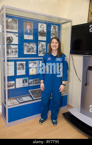 International Space Station Expedition 59 crew member Christina Koch of NASA poses in front of a display housing memorabilia from the flight of the first woman to fly in space, Valentina Tereshkova, at the Baikonur Cosmodrome March 10, 2019 in Baikonur, Kazakhstan. Expedition 59 crew: Christina Koch of NASA, Alexey Ovchinin of Roscosmos, and Nick Hague of NASA will launch March 14th onboard the Soyuz MS-12 spacecraft for a six-and-a-half month mission on the International Space Station. - Stock Image