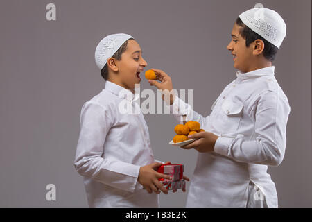 Young Muslim boy feeding other Muslim boy with sweets - Stock Image