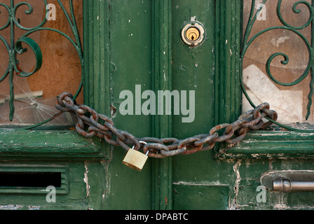 Detail of an old, green door, chained up with padlock - Stock Image