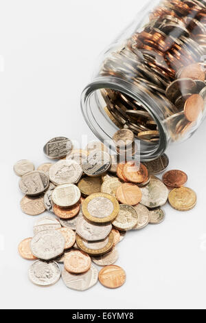 Coins falling-out of saving jar - Stock Image